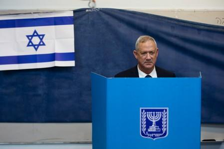 Leader of Blue and White party, Benny Gantz stands behind a voting booth as he votes in Israel's parliamentary election at a polling station in Rosh Ha'ayin, Israel