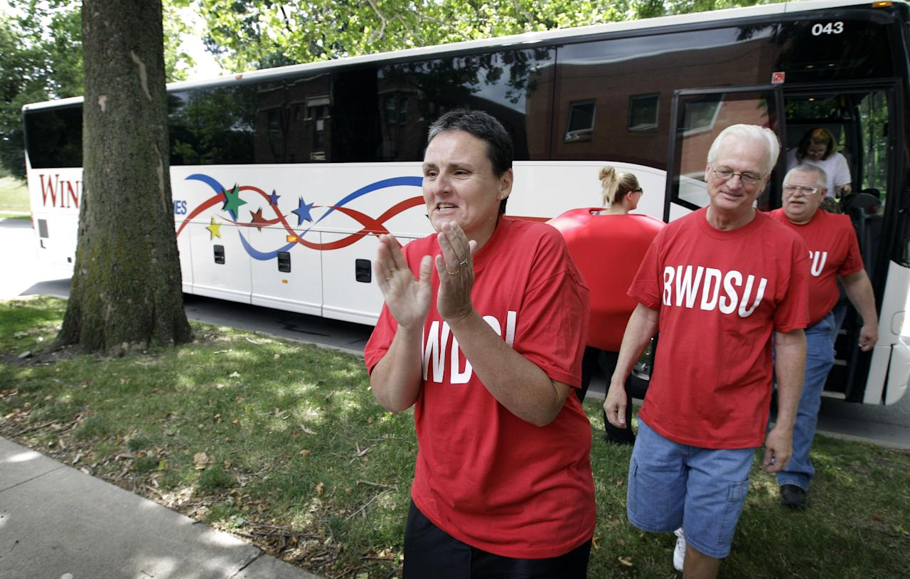 Workers from the Quaker Oats plant in Cedar Rapids, Iowa, step off the bus as they arrive to cash in their winning $241 million Powerball ticket at the Iowa Lottery headquarters, Wednesday, June 20, 2012, in Des Moines, Iowa. Lottery spokeswoman Mary Neubauer says one of the workers bought the winning ticket for the group for the June 13 drawing and the winnings will be split 20 ways.(AP Photo/Charlie Neibergall)