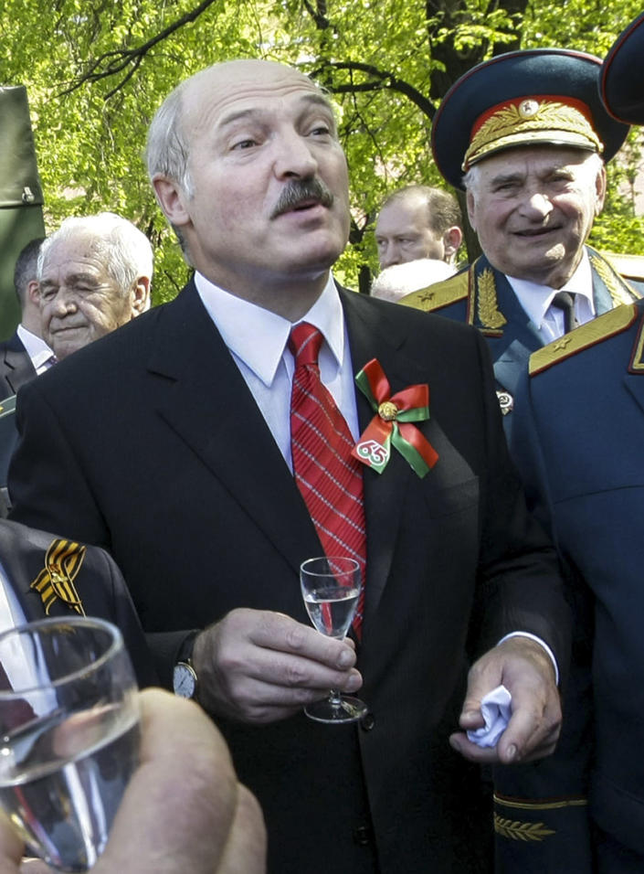 "FILE In this file pool photo taken on Saturday, May 8, 2010, Belarusian President Alexander Lukashenko toasts with World War II veterans during an unveiling ceremony of the monument to the cities of military glory near the Tomb of Unknown Soldier at the Kremlin wall on the eve of the Victory Day in Moscow, Russia. The 65-year-old former state farm director advised the Belarusians to ""kill the virus with vodka,"" go to sauna and work in the fields to stay healthy. ""Tractors will cure everybody!"" he exclaimed once. (Vladimir Rodionov, Sputnik, Kremlin Pool Photo via AP, File)"