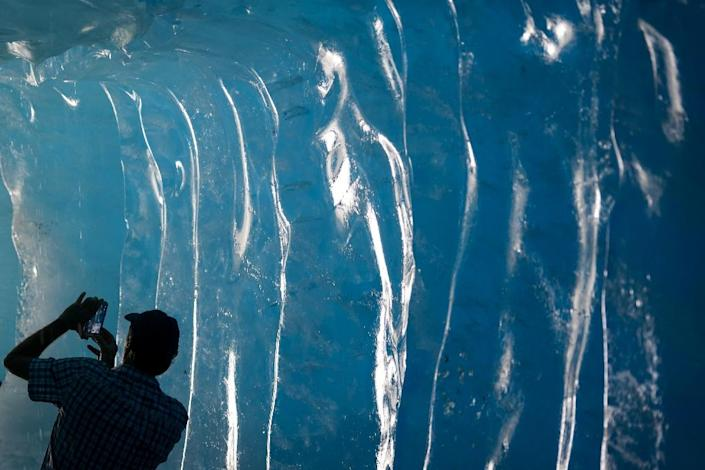 A tourist takes pictures inside an ice cave inside the Rhone Glacier near Gletsch (AFP Photo/Fabrice Coffrini)