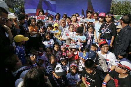 Protest leader Suthep Thaugsuban (C) is surrounded by children as others take pictures inside the anti-government encampment in front of Democracy monument in Bangkok January 11, 2014. EUTERS/Damir Sagolj