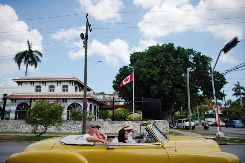 Tourists riding in a vintage car pass in front of Canada's Embassy in Havana, Cuba, May 9, 2019. REUTERS/Alexandre Meneghini