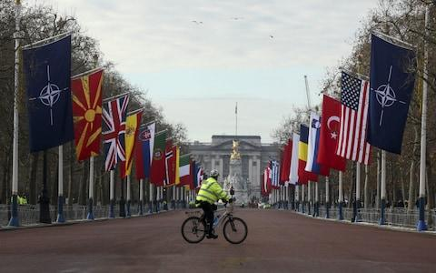 A British police officer cycles along The Mall past the flags of Nato - Credit: Simon Dawson/Bloomberg