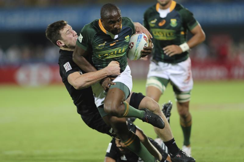 South Africa's Siviwe Soyizwapi runs with the ball as New Zealand's players try to stop him in the final match of the Emirates Airline Rugby Sevens in Dubai, United Arab Emirates, Saturday, Dec.7, 2019. (AP Photo/Kamran Jebreili)