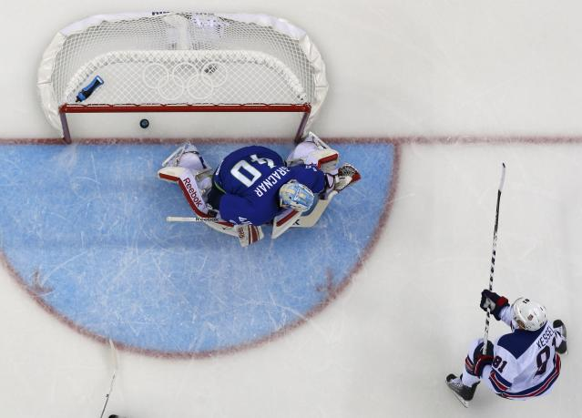 Team USA's Kessel scores a goal on Slovenia's goalie Gracnar during the first period of their men's preliminary round ice hockey game at the 2014 Sochi Winter Olympics