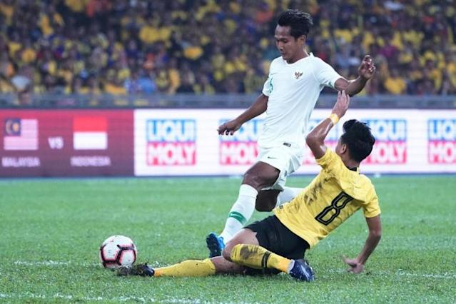 Malaysia's Muhamad Nor Azam tries to escape a tackle from Indonesia's Hendro Siswanto in as the home team win Kuala Lumpur (AFP Photo/STR)