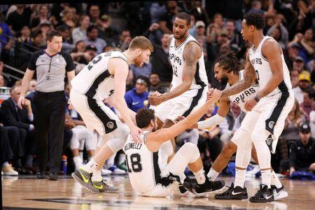 Mar 18, 2019; San Antonio, TX, USA; San Antonio Spurs shooting guard Marco Belinelli (18) is helped up by teammates Davis Bertans (left), LaMarcus Aldridge (12), Patty Mills (8), and DeMar DeRozan (10) after making a three point basket during the second half  against the Golden State Warriors at AT&T Center. Mandatory Credit: Soobum Im-USA TODAY Sports