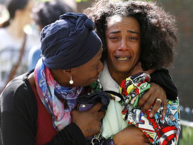 Pretana Morgan, right, the mother of shooting victim Rhyhiem Ainsworth Barton, 17, pictured being comforted by a family friend (Reuters)