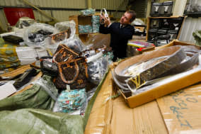 Embargoed to 0001 Friday December 6Higher Officer Sean Gigg of the Border Force inspects a warehouse full of seized counterfeit goods at Southampton docks. PRESS ASSOCIATION Photo. Picture date: Thursday December 5, 2013. Border Force and Trading Standards have today launched a public campaign warning festive shoppers to be careful about what they buy and where they buy it from to avoid fuelling the illegal trade in counterfeit goods. Photo credit should read: Chris Ison/PA Wire
