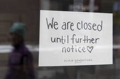 A sign on a store window says it's closed until further notice.