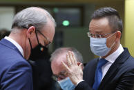 Hungary's Foreign Minister Peter Szijjarto, right, speaks with Ireland's Foreign Minister Simon Coveney during a meeting of EU foreign ministers at the European Council building in Brussels, Monday, Feb 22, 2021. European Union foreign ministers on Monday will look at options for imposing fresh sanctions against Russia over the jailing of opposition leader Alexei Navalny as the 27-nation bloc considers the future of its troubled ties with the country. (Yves Herman, Pool via AP)