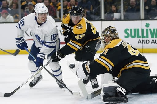 Toronto Maple Leafs' Andreas Johnsson (18) looks for the rebound after taking a shot on Boston Bruins' Jaroslav Halak (41) as Torey Krug (47) defends during the first period of an NHL hockey game in Boston, Saturday, Dec. 8, 2018. (AP Photo/Michael Dwyer)