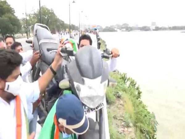 Youth Congress leaders throw a two-wheeler in Hussain sagar as mark of protest against fuel price hike in Hyderabad on Friday.
