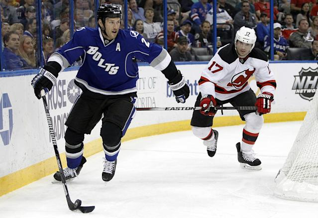 Tampa Bay Lightning defenseman Eric Brewer (2) controls the puck ahead of New Jersey Devils right wing Michael Ryder (17) during the first period of an NHL hockey game Saturday, March 15, 2014, in Tampa, Fla. (AP Photo/Brian Blanco)