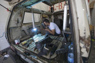 A welder converts a van into a food truck, at a workshop in the West Bank city of Ramallah, Tuesday, Sept. 22, 2020. With dine-in restaurants mostly closed due to health restrictions, food trucks have allowed Palestinian entrepreneurial businessmen to find a way to keep working. (AP Photo/Nasser Nasser)