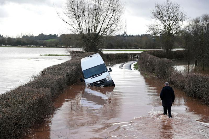 <strong>A man makes his through floodwater past an abandoned vehicle near the village of Hampton Bishop near Hereford, after the River Lugg burst its banks.</strong> (Photo: ASSOCIATED PRESS)