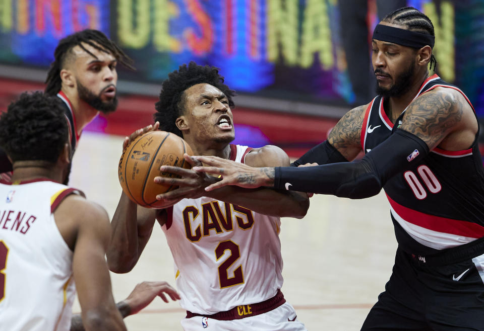 Cleveland Cavaliers guard Collin Sexton, left, is fouled by Portland Trail Blazers forward Carmelo Anthony during the first half of an NBA basketball game in Portland, Ore., Friday, Feb. 12, 2021. (AP Photo/Craig Mitchelldyer)