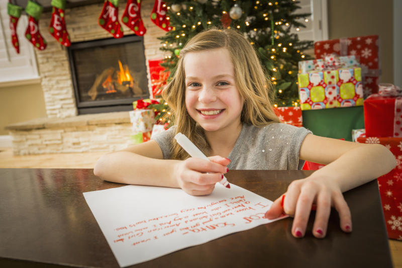 Caucasian girl writing to Santa at Christmas