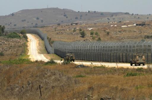 Israeli army vehicles patrol the border fence with Syria in the Golan Heights