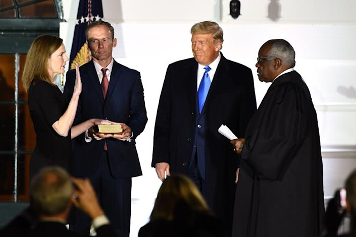 President Donald Trump watches as Supreme Court Justice Clarence Thomas swears in Justice Amy Coney Barrett on Oct. 26, 2020.