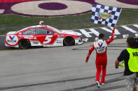Kyle Larson walks back to his car with the checkered flag after winning a NASCAR Cup Series auto race Sunday, June 20, 2021, in Lebanon, Tenn. (AP Photo/John Amis)