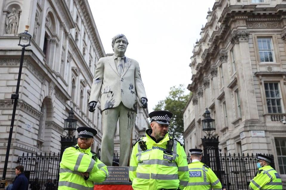 Police officers stand next to a statue stained with oil (REUTERS)