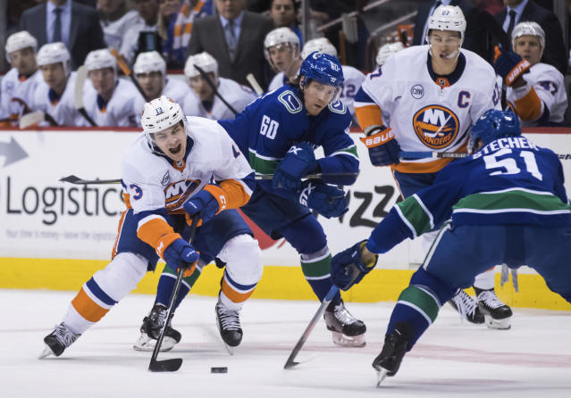 New York Islanders' Mathew Barzal, left, reaches for the puck in front of Vancouver Canucks' Markus Granlund (60), of Finland, as Canucks' Troy Stecher (51) and Islanders' Anders Lee, back right, watch during the first period of an NHL hockey game Saturday, Feb. 23, 2019, in Vancouver, British Columbia. (Darryl Dyck/The Canadian Press via AP)