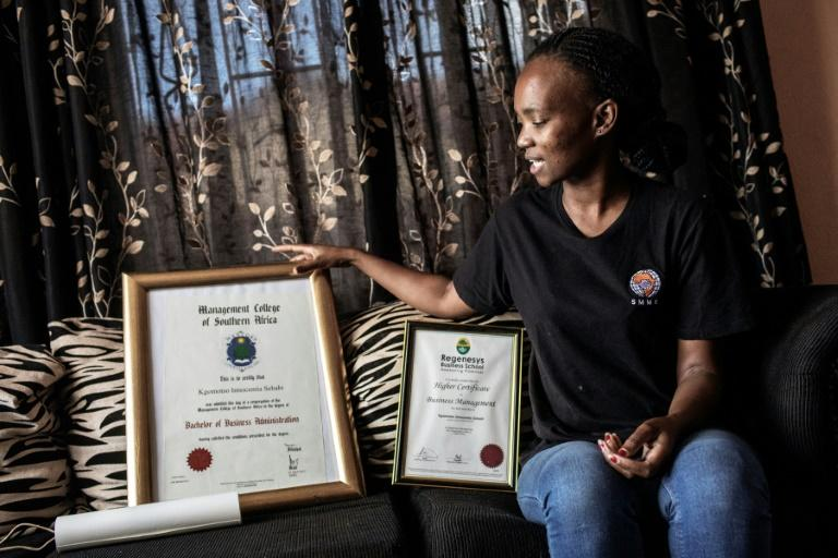 Kgomotso Sebabi, a South African unemployed graduate shows her higher education certificate