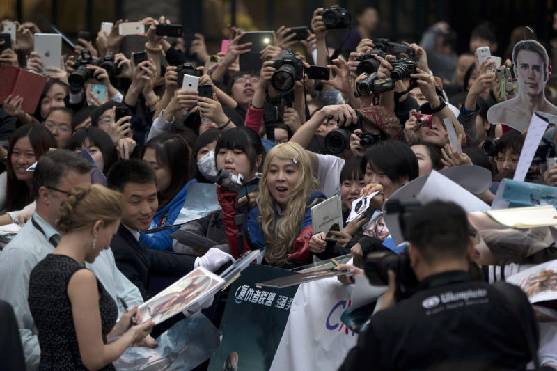 """In this Monday, March 24, 2014 photo, fans watch actress Scarlett Johansson, left in foreground, sign her autograph during a publicity event ahead of the April release of her movie """"Captain America: The Winter Soldier"""" in Beijing. Captain America and Spiderman are seeking to dominate the Chinese box office in the coming weeks, proving that U.S. patriotic superheroes can overcome China's leeriness of foreign films if they promise big money. Chinese authorities, wary of outside cultural influences and competition, restrict the number of foreign movies shown in the mainland's cinemas to 34 each year. (AP Photo/Ng Han Guan)"""
