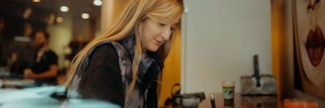 woman with long blonde hair writing in a coffee shop