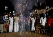 Villagers release firecrackers and hold placards featuring U.S. Vice President Kamala Harris after her inauguration, in Thulasendrapuram, the hometown of Harris' maternal grandfather, south of Chennai, Tamil Nadu state, India, Wednesday, Jan. 20, 2021. Residents of a tiny Indian village surrounded by rice paddies flocked to a Hindu temple, setting off firecrackers and praying and as they watched Kamala Harris, who has strong roots to the village, take her oath of office and become the U.S. vice president on Wednesday. (AP Photo/Aijaz Rahi)