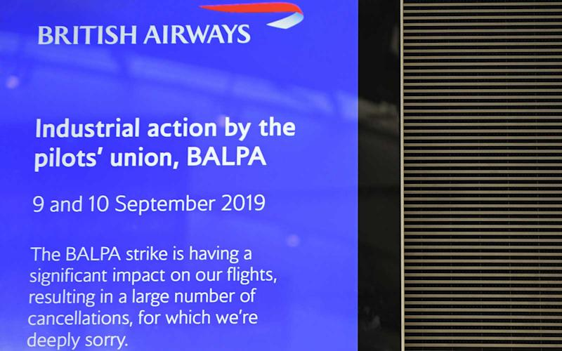 A British Airways sign displays information on industrial actionn in the near-deserted departure area at Heathrow airport Terminal 5 in west London on September 9, 2019, as the airline's first-ever pilots' strike began. | BEN STANSALL/Getty Images