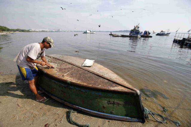 A fisherman cleans his boat on Fundao beach in the Guanabara Bay in Rio de Janeiro