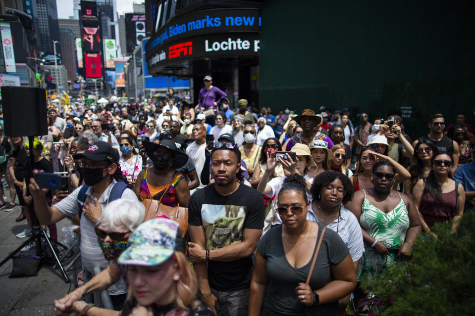 People try to see a free outdoor event organized by The Broadway League as celebrations take place during Juneteenth at Times Square on Saturday, June 19, 2021, in New York. Parades, picnics and lessons in history marked Juneteenth celebrations in the U.S., a day that marks the arrival of news to enslaved Black people in a Texas town that the Confederacy had surrendered in 1865 and they were free. (AP Photo/Eduardo Munoz Alvarez)