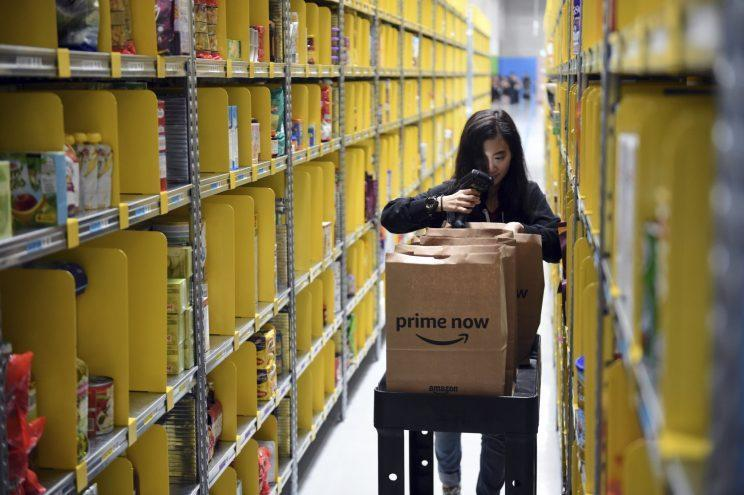 A staff member collects merchandise for customers' orders from shelves at the newly-opened Amazon Prime Now facility in Singapore Thursday, July 27, 2017. Amazon introduced express delivery in Singapore in its first direct effort to win over Southeast Asian digital natives and new internet users. The American e-commerce company announced Thursday it will begin operating a 100,000 square foot (9,290 square meter) distribution facility in the wealthy island nation. (AP Photo/Joseph Nair)