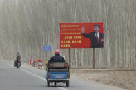 """Chinese President Xi Jinping is seen on a billboard with the slogan, """"Administer Xinjiang according to law, unite and stabilize the territory, culturally moisturize the territory, enrich the people and rejuvenate the territory, and build the territory for a long term,"""" in Yarkent County in northwestern China's Xinjiang Uyghur Autonomous Region on March 21, 2021. Four years after Beijing's brutal crackdown on largely Muslim minorities native to Xinjiang, Chinese authorities are dialing back the region's high-tech police state and stepping up tourism. But even as a sense of normality returns, fear remains, hidden but pervasive. (AP Photo/Ng Han Guan)"""