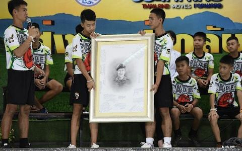 Rescued Thai football coach Ekkapol Chantawong (L) together with 12 children pays tribute to the Navy Seal who died during their rescue - Credit: AFP