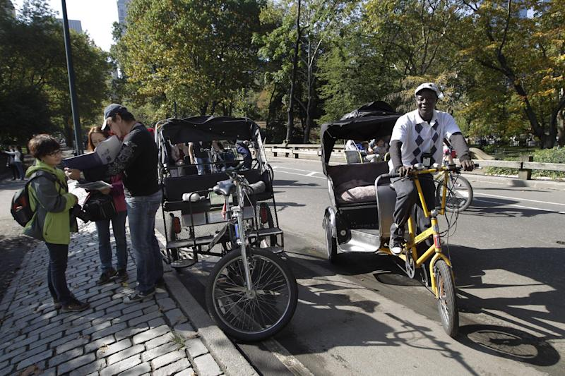 In this Saturday, Oct. 20 2012 photo, a pedicab driver, left, shows potential customers a map with of the tour of New York's Central Park while another looks for customers. Ever since a Texas family paid a pedicab driver $442 to ride 14 blocks in New York City this summer, city officials have been pushing for a simplified pricing structure so tourists don't get taken for a ride. (AP Photo/Mary Altaffer)