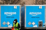 A worker in a face mask walks by trucks parked at an Amazon facility as the global coronavirus outbreak continued in Bethpage on Long Island in New York