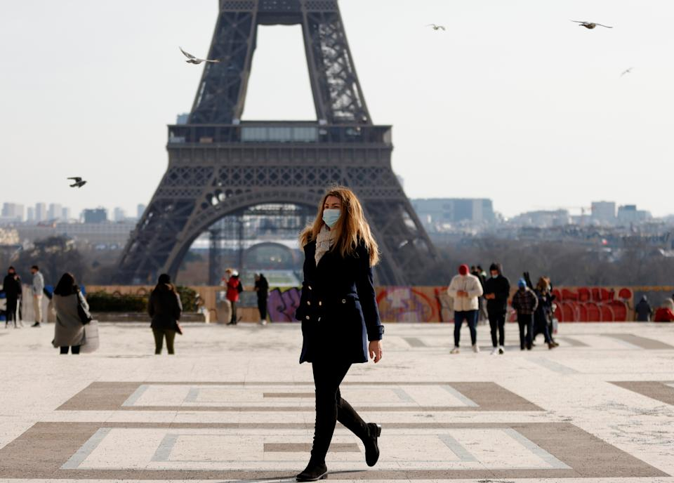 A woman, wearing protective face masks, walks in front of the Eiffel tower at the Trocadero in Paris amid the coronavirus disease (COVID-19) outbreak in France, February 11, 2021. REUTERS/Sarah Meyssonnier