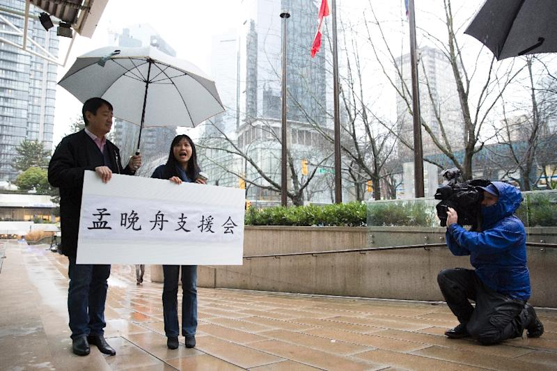 Terence Xu (L) and Ada Yu hold a sign in support of Meng outside her bail hearing (AFP Photo/Jason Redmond)