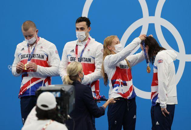 Anna Hopkin presents Kathleen Dawson of Team Great Britain with her medal during the ceremony for the mixed 4 x 100 meter medley relay on July 31. (Photo: Ian MacNicol via Getty Images)