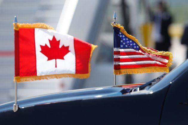 A limousine drives with U.S. and Canadian flags before the arrival of U.S. President Donald Trump at Canadian Forces Base Bagotville in Bagotville, Que. on June 8, 2018 for G7 summit.