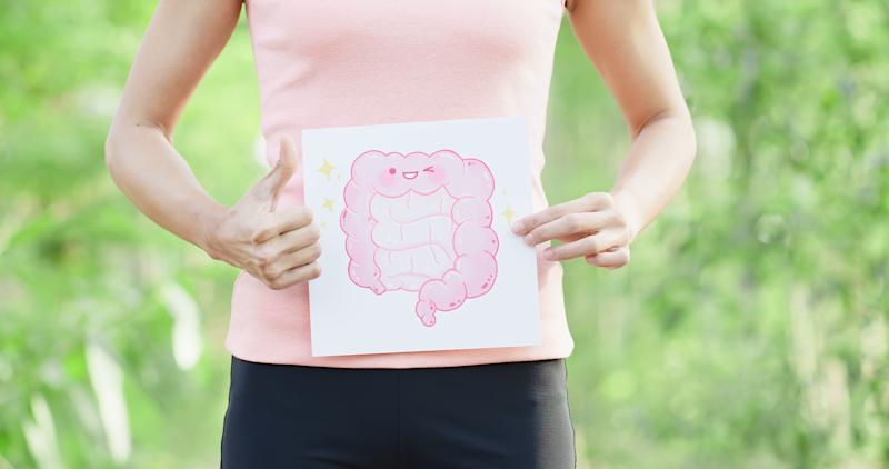 Woman holding a drawing of a smiling colon while giving a thumbs up.