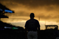 Colorado Rockies first base coach Ronnie Gideon stands on the field as the setting sun illuminates clouds during the third inning of the Rockies' baseball game against the Milwaukee Brewers on Saturday, June 19, 2021, in Denver. (AP Photo/David Zalubowski)