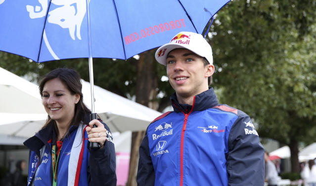 Toro Rosso driver Pierre Gasly, right, of France is kept dry with an umbrella as he arrives at the Australian Formula One Grand Prix in Melbourne, Saturday, March 24, 2018. The first race of the 2018 seasons is on Sunday. (AP Photo/Asanka Brendon Ratnayake)