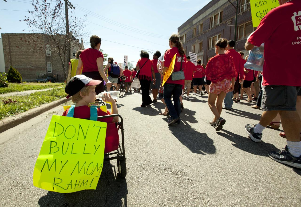 A young boy in a cart is pulled along by his mother at the tail of a group of public school teachers marching on streets surrounding John Marshall Metropolitan High School on Wednesday, Sept. 12, 2012 in West Chicago. Teachers walked off the job Monday for the first time in 25 years over issues that include pay raises, classroom conditions, job security and teacher evaluations. (AP Photo/Sitthixay Ditthavong)