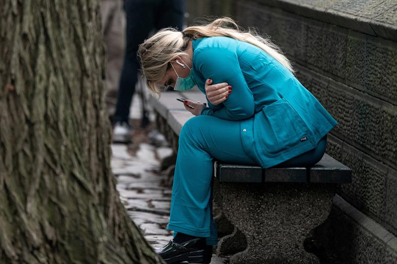 Image: A healthcare worker sits on a bench near Central park in the Manhattan borough of New York City (Jeenah Moon / Reuters)