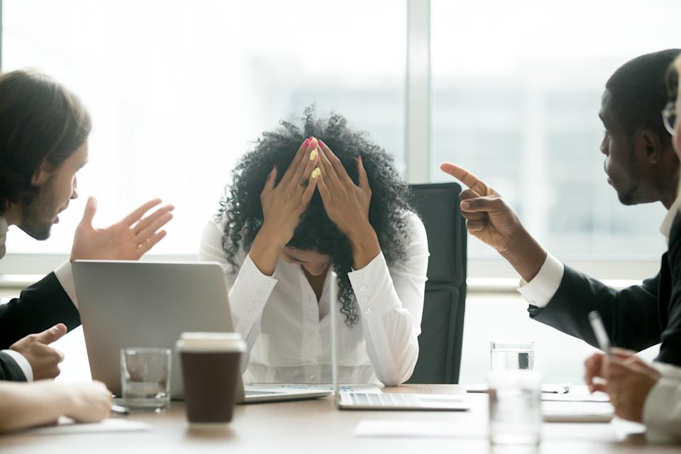 Upset depressed black woman leader suffering from gender discrimination inequality at work, diverse men colleagues pointing fingers scolding bullying frustrated african businesswoman at workplace