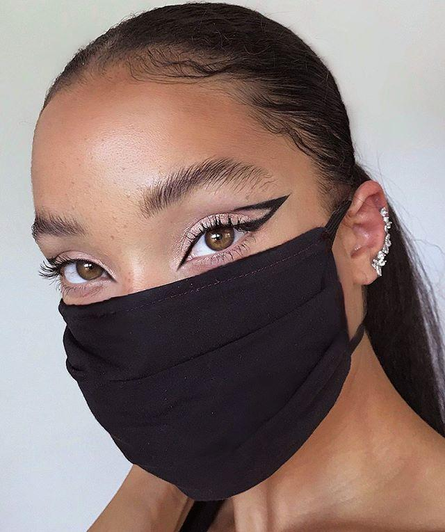 "<p>Draw attention to the star of the face (your eyes!) with this negative space cat eye. The black liner pairs perfectly with a black mask. Black is the new black. </p><p><a href=""https://www.instagram.com/p/CCJQwifhpUV/"" rel=""nofollow noopener"" target=""_blank"" data-ylk=""slk:See the original post on Instagram"" class=""link rapid-noclick-resp"">See the original post on Instagram</a></p>"